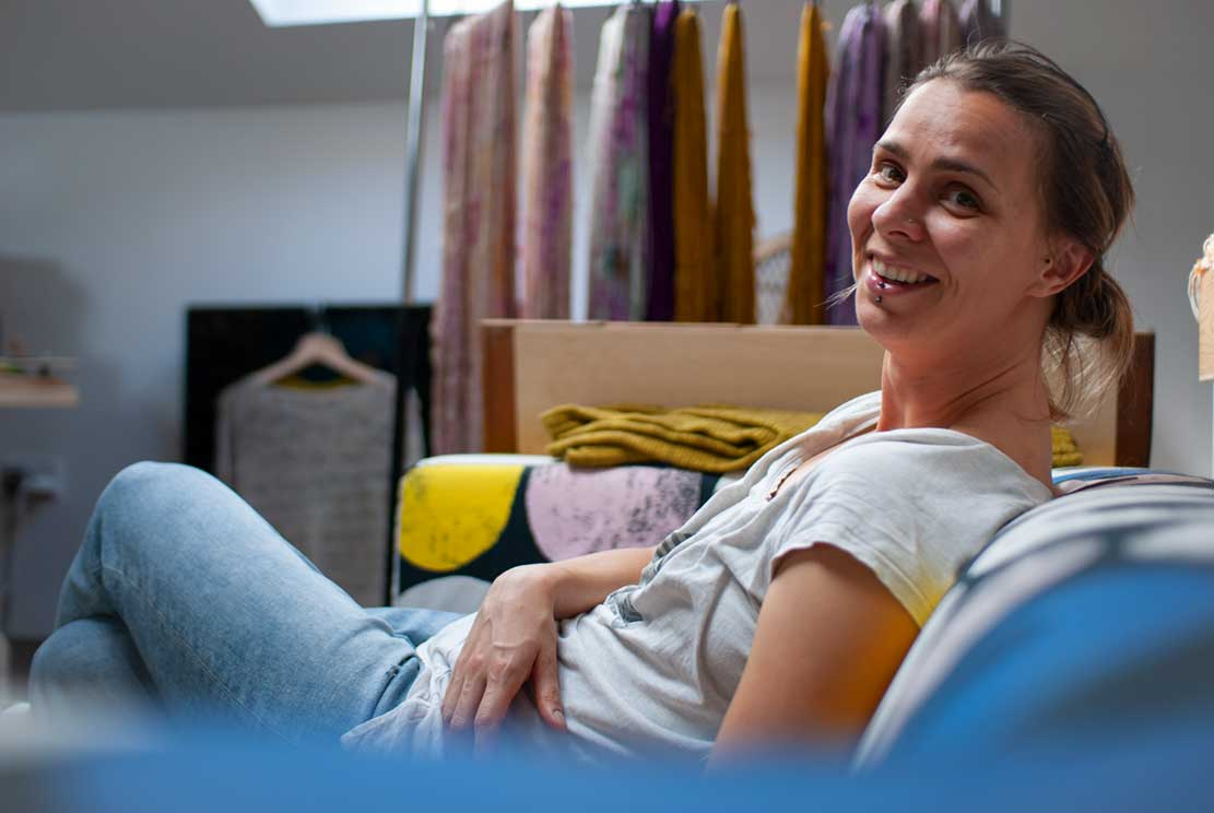our friend Petra sitting comfortably on a sofa in her yarn studio