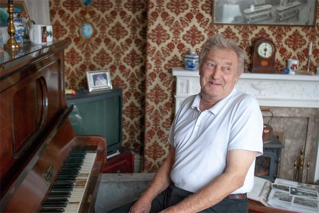 John (69), like Jozef's father, sitting behind a piano turned towards you smiling.