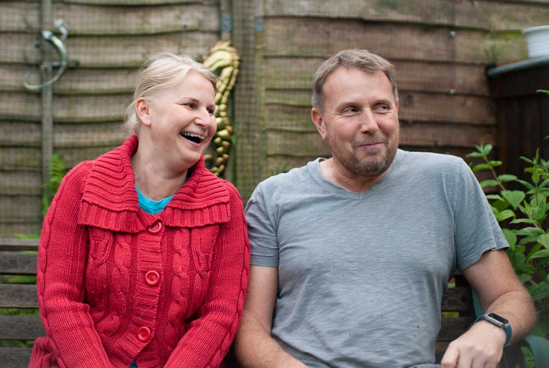 Katka and Kevin sitting and smiling in their garden