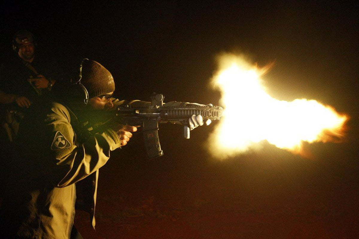 an angry man shooting from a firearm night time flames out of its barrel