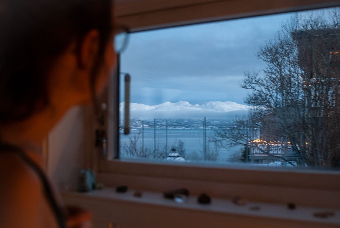 young woman looking out of a window towards snowed mountains on Ringvassøya island close by city of Tromsø