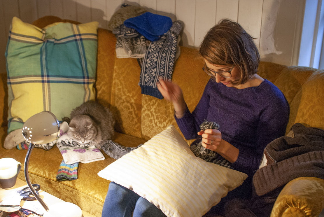 young-woman,-called-Meline,-sits-on-a-sofa-with-a-cat-and-mends-socks-under-lamp-feeling-cosy